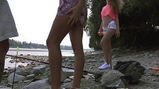 Two girls are blowing dicks outdoors